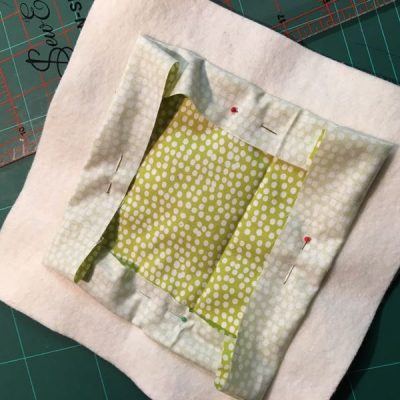 Quilt backing pinned back to expose batting